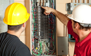 image of electrician testing electrical panel